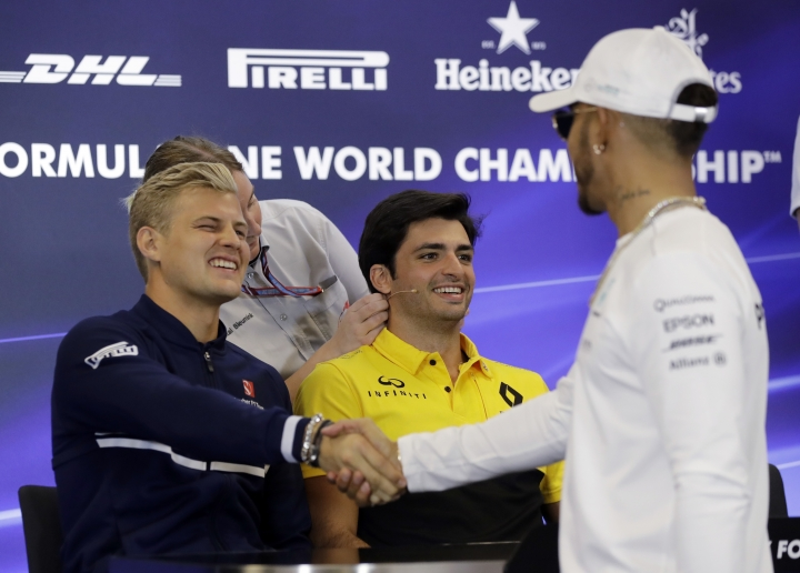 Sauber driver Marcus Ericsson, left, of Sweden, shakes hands with Mercedes driver Lewis Hamilton, of Britain, before a news conference for the Formula One U.S. Grand Prix auto race at the Circuit of the Americas, Thursday, Oct. 19, 2017, in Austin, Texas. (AP Photo/Eric Gay)