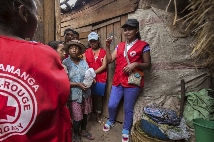 Red Cross volunteers talk to villagers about the plague outbreak, 30 miles west of Antananarivo, Madagascar, Monday, Oct. 16, 2017. As plague cases rose last week in Madagascar's capital, many city dwellers panicked. They waited in long lines for antibiotics at pharmacies and reached through bus windows to buy masks from street vendors. Schools have been canceled, and public gatherings are banned. (AP Photo/Alexander Joe)