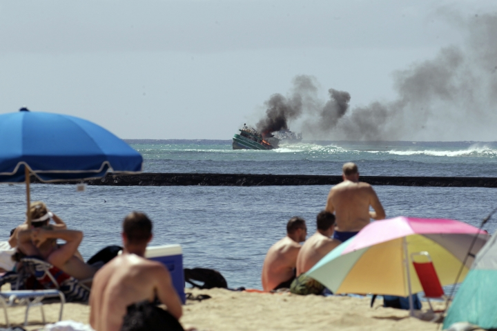"""FILE -A grounded 79 ft fishing boat called """"Pacific Paradise"""" caught fire on Saturday, Oct. 14, 2017, shortly after 10 am near Kaimana Beach in Honolulu. No injuries were reported. A boat that ran aground off Honolulu while transporting foreign fishermen to work in Hawaii's commercial fishing industry has raised new questions about the safety and working conditions for foreign laborers in this unique U.S. fleet. A long, cramped journey to the United States for a group of fishermen from Vietnam, Indonesia, Philippines and Kirabati ended last week with a rescue by the U.S. Coast Guard after their fishing vessel smashed into a reef just off Waikiki's shore.(Cindy Ellen Russell /The Star-Advertiser via AP, File)"""