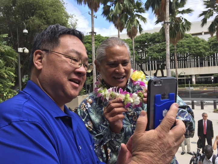 Former Honolulu police chief Louis Kealoha, right, shows off his flower lei outside U.S. District Court in Honolulu on Friday, Oct. 20, 2017. Louise Kealoha, his wife city deputy prosecutor Katherine Kealoha, and current and former police officers conspired to frame the couple's relative for stealing a mailbox to discredit him in a family financial dispute, according to a federal indictment released Friday. (AP Photo/Audrey McAvoy)