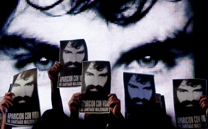 FILE - In this Sept. 1, 2017 file photo, demonstrators hold up posters of missing activist Santiago Maldonado, during a protest at Plaza de Mayo in Buenos Aires, Argentina. Sergio Maldonado confirmed on Friday, Oct. 20, 2017, to journalists that the body found in a Patagonia river is that of his missing brother, Santiago Maldonado. (AP Photo/Natacha Pisarenko, File)