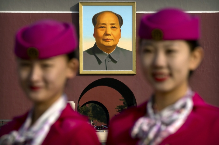 Hospitality staff members pose for a group photo near the large portrait of Mao Zedong on Tiananmen Gate before the closing ceremony of China's 19th Party Congress at the Great Hall of the People in Beijing, Tuesday, Oct. 24, 2017. The ruling Communist Party on Tuesday formally lifted Xi Jinping's status to China's most powerful ruler in decades, setting the stage for the authoritarian leader to tighten his grip over the country while pursuing an increasingly muscular foreign policy and military expansion. (AP Photo/Mark Schiefelbein)