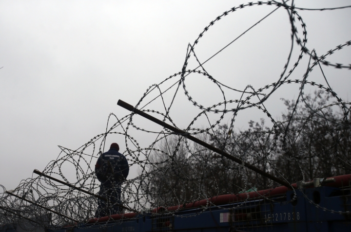 """FILE - In this Wednesday, Feb. 8, 2017 file photo, a Hungarian police officer stands guard at Serbia's border with Hungary near a makeshift camp for migrants in Horgos, Serbia. The European Union must do more to defend its external borders against migrants, EU chief Donald Tusk said Tuesday, describing Europe as a """"cultural community"""" whose heritage must be preserved. (AP Photo/Darko Vojinovic, File)"""