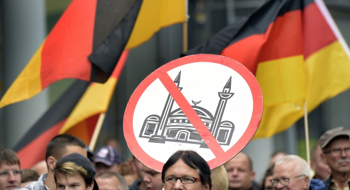 """FILE - In this Sunday, Sept 18, 2016 file photo, people take part in a demonstration in the east German city of Bautzen, after clashes between far-right protesters and migrants. The European Union must do more to defend its external borders against migrants, EU chief Donald Tusk said Tuesday, Oct. 24, 2017 describing Europe as a """"cultural community"""" whose heritage must be preserved. Recent elections in Germany and Austria have reflected rising support for anti-migrant parties. (AP Photo/Jens Meyer, File)"""