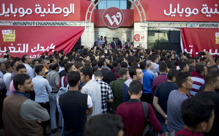 Palestinians wait for the opening of the main branch of the new cellular network company, Wataniya Mobile, a subsidiary of Qatar's Ooredoo, in Gaza City, Tuesday, Oct. 24, 2017. Until now, Gaza has only been served by one operator, Jawwal, which was launched in the Palestinian territories in 1999. (AP Photo/ Khalil Hamra)