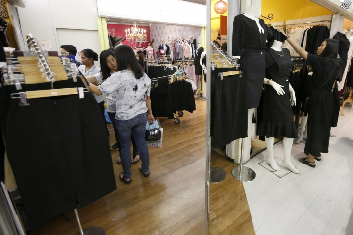 In this Monday, Oct. 23, 2017, photo, customers are reflected in a mirror while buying black clothing in honor of the late Thai King Bhumibol Adulyadej at a shopping mall in Bangkok, Thailand. The exactingly planned five-day funeral for Bhumibol will be governed by strict protocols for how the public and media conduct themselves that are as much about honoring the late king as they are about controlling a delicate political moment. Formal dress requirements that are typical for close quarters contact with members of the royal family include a prohibition on earrings, beards or mustaches for men, and unnatural hair coloring for women. (AP Photo/Sakchai Lalit)