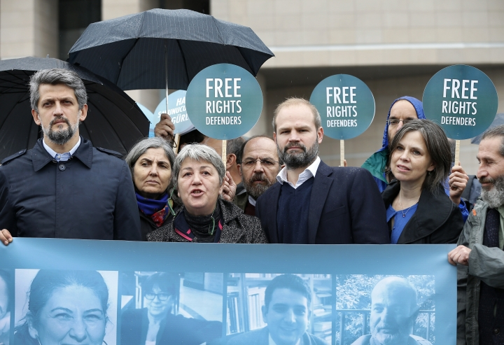 "Activists talk to the media as they stage a protest outside a court in Istanbul, Wednesday, Oct. 25, 2017. Eleven human rights activists, including the two local heads of Amnesty International, are going on trial, accused of belonging to and aiding terror groups. Human rights groups say the defendants, who face up to 15 years in prison, have been accused of ""trumped up"" charges. (AP Photo/Lefteris Pitarakis)"