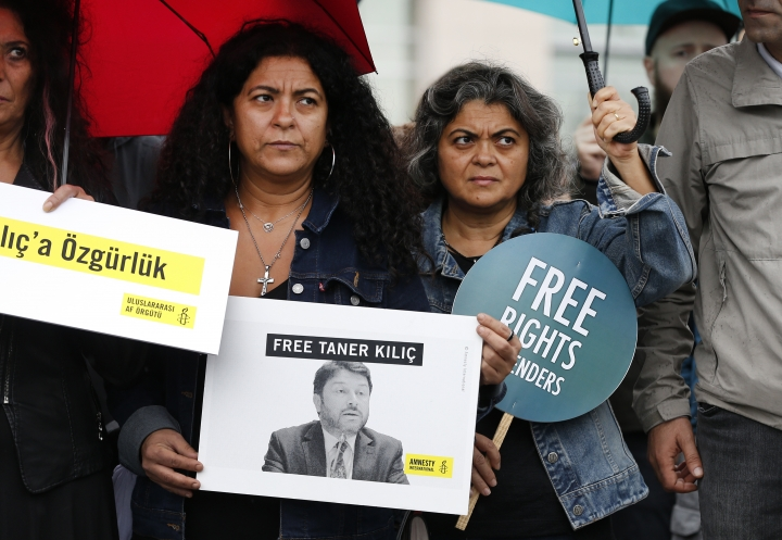 Human rights activists stage a protest outside a court in Istanbul, Wednesday, Oct. 25, 2017 where eleven human rights activists go on trial, accused of belonging to and aiding terror groups. They hold placards demanding the release of Amnesty's Turkey chairman Taner Kilic, who was imprisoned separately in June, and goes on trial in the city of Izmir for alleged links to U.S.-based cleric Fethullah Gulen, blamed by the government for last year's coup attempt. (AP Photo/Lefteris Pitarakis)