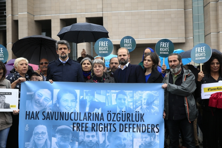 "Human rights activists stage a protest, holding a banner reading in Turkish ""Free right defenders"" outside a court in Istanbul, Wednesday, Oct. 25, 2017. Eleven human rights activists, including the two local heads of Amnesty International, are going on trial, accused of belonging to and aiding terror groups. Human rights groups say the defendants, who face up to 15 years in prison, have been accused of ""trumped up"" charges. (AP Photo/Lefteris Pitarakis)"