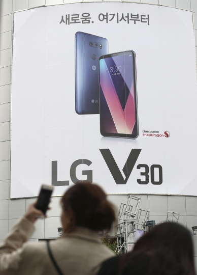 A woman holds her smartphone near an advertisement of LG Electronics V30 smartphone in Seoul, South Korea, Thursday, Oct. 26, 2017. LG Electronics Inc. says its mobile business lost money for a second straight quarter as component prices rose. (AP Photo/Lee Jin-man)