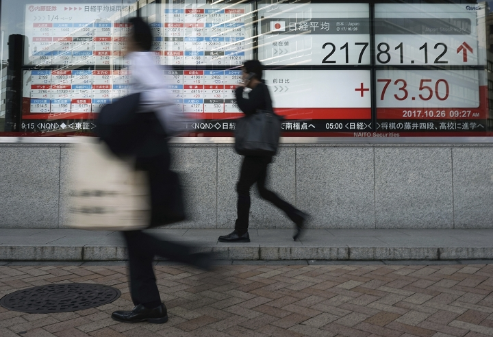 Men walk past an electronic stock board showing Japan's Nikkei 225 index at a securities firm in Tokyo Thursday, Oct. 26, 2017. Asian shares were drifting Thursday as Wall Street's retreat from recent record highs and a widely awaited European Central Bank meeting gave investors reason to pause. (AP Photo/Eugene Hoshiko)
