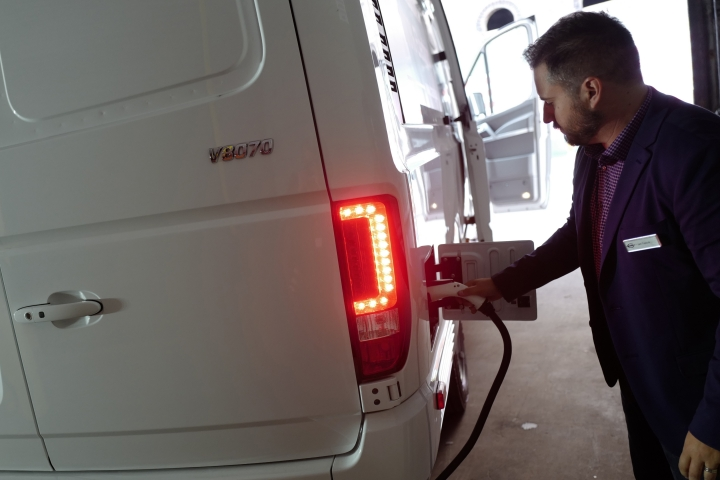 Ian Televise, the head of marketing for Chanje, demonstrates the re-charging port on the company's V8070 electric medium-duty truck, Thursday, Nov. 2, 2017, in New York. The vehicle can carry a load of up to 6,000 pounds for a distance of about 100 miles on a single charge. Truck rental company Ryder Systems Inc. is adding 125 of the fully electric vans to its fleet. (AP Photo/Mark Lennihan)