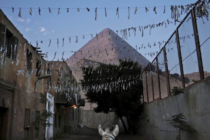 FILE - In this Nov. 17, 2016 file photo, a horse walks near the Great Pyramid, in Giza, Egypt. Scientists have found a previously undiscovered hidden chamber in Egypt's Great Pyramid of Giza, the first such discovery in the structure since the 19th century. In a report published in the journal Nature on Thursday, Nov. 2, 2017, an international team says the 30-meter (yard) void deep within the pyramid is situated above the Grand Gallery, and has a similar cross-section. (AP Photo/Nariman El-Mofty, File)