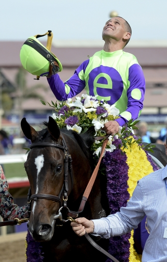 Javier Castellano, top, celebrates after riding Rushing Fall to victory in the Juvenile Fillies Turf horse race during the first day of the Breeders' Cup, Friday, Nov. 3, 2017, in Del Mar, Calif. (AP Photo/Denis Poroy)