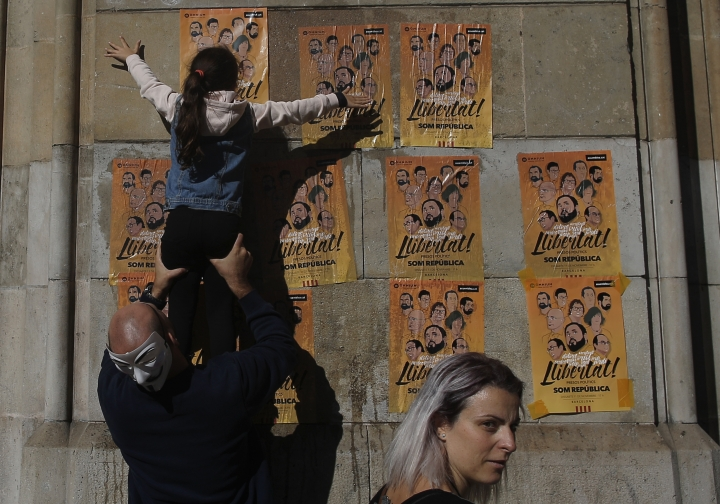 "A girl pastes a banner on a wall that reads in Catalan: ""Freedom for the Political Prisoners"", during a protest against the decision of a judge to jail ex-members of the Catalan government at the University square in Barcelona, Spain, Sunday, Nov. 5, 2017. A Spanish judge issued an international arrest warrant on Friday for former members of the Catalan Cabinet who were last seen in Brussels, including the ousted separatist leader Carles Puigdemont, who said he was prepared to run for his old job even while battling extradition in Belgium. (AP Photo/Manu Fernandez)"