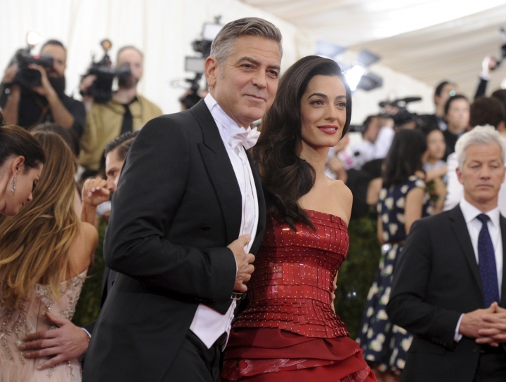 "FILE - In this May 4, 2015, file photo, George Clooney and Amal Clooney arrive at The Metropolitan Museum of Art's Costume Institute benefit gala celebrating ""China: Through the Looking Glass"" in New York. The Met announced on Nov. 8, 2017, that Amal Clooney, Rihanna, Donatella Versace and Anna Wintour will serve as co-chairs of next year's event. (Photo by Evan Agostini/Invision/AP, File)"
