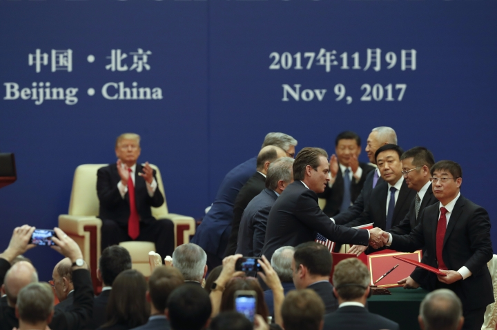 Chinese and U.S. business delegates exchange memorandum of understanding as U.S. President Donald Trump and Chinese Xi Jinping clap in the background during a business event at the Great Hall of the People in Beijing, Thursday, Nov. 9, 2017. Trump is on a five-country trip through Asia traveling to Japan, South Korea, China, Vietnam and the Philippines. (AP Photo/Andy Wong)