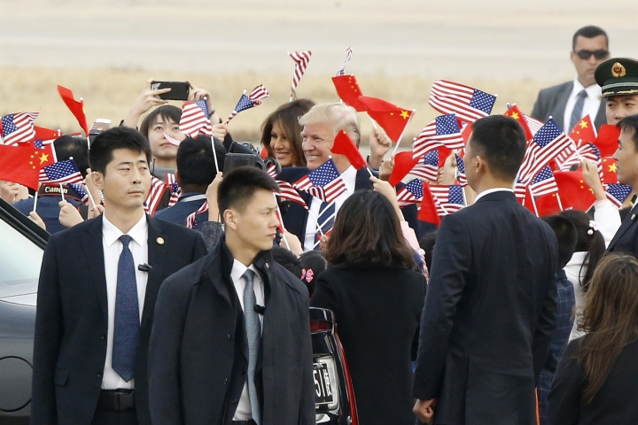 U.S. President Donald Trump and first lady Melania Trump, center, are greeted as they arrive on Air Force One in Beijing, China, Wednesday, Nov. 8, 2017. (Thomas Peter/Pool Photo via AP)