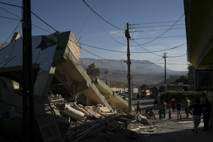 People walk next to a destroyed house after an earthquake in the city of Darbandikhan, northern Iraq, Monday, Nov. 13, 2017. Authorities reported that a powerful 7.3 magnitude earthquake struck the Iraq-Iran border region on Monday and killed more than three hundred people in both countries, sent people fleeing their homes into the night and was felt far west as the Mediterranean coast. (AP Photo/Felipe Dana)