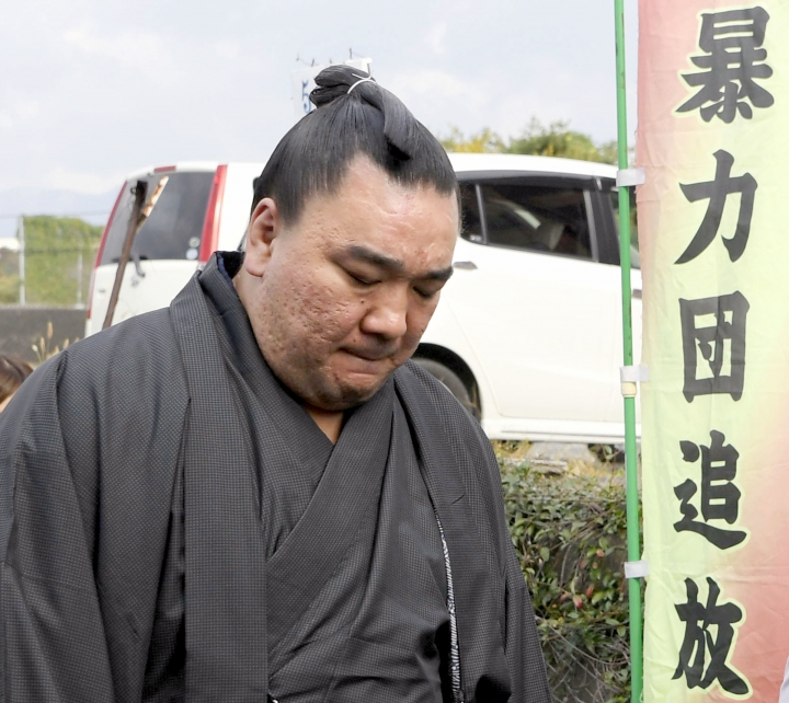 "Mongolian sumo grand champion Harumafuji looks at the ground as he leaves after visiting wrestler Takanoiwa's stable master's quarters in Tagawa, southwestern Japan, Tuesday, Nov. 14, 2017. Japanese sumo officials are investigating allegations that Harumafuji hit his fellow Mongolian wrestler Takanoiwa in the head with a beer bottle at a party in October, fracturing his skull base and causing other injuries. A campaign banner at right reads: ""Run gang out."" (Nozomi Endo/Kyodo News via AP)"