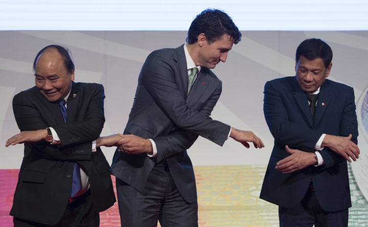 Canadian Prime Minister Justin Trudeau, center, shakes hands with Vietnamese Prime Minister Nguyen Xuan Phuc, left, and Philippine President Rodrigo Duterte during a photo session of the ASEAN-Canada 40th Commemorative session in Manila, Philippines, Tuesday, Nov. 14, 2017. (Adrian Wyld/The Canadian Press via AP)