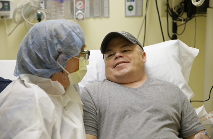 """Brian Madeux, 44, sitting with his girlfriend Marcie Humphrey, waits to receive the first human gene editing therapy for NPS, at the UCSF Benioff Children's Hospital in Oakland, Calif., on Monday, Nov. 6, 2017. Through an IV, Madeux will receive billions of copies of a corrective gene and a genetic tool to cut his DNA in a precise spot. """"It's kind of humbling"""" to be the first to test this, said Madeux, who has a metabolic disease called Hunter syndrome. (AP Photo/Eric Risberg)"""