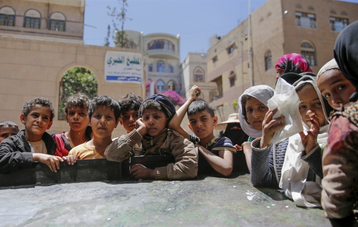 FILE - In this April, 13, 2017 file photo, Yemeni children wait to receive food rations provided by a local charity, in Sanaa, Yemen. Save the Children, an international aid group said late Wednesday, Nov. 15, 2017, that an estimated 130 children or more die every day in war-torn Yemen from extreme hunger and disease. It said a continuing blockade by the Saudi-led coalition fighting Yemen's Shiite rebels is likely to further increase the death rate and that over 50,000 children are believed to have died in 2017. (AP Photo/Hani Mohammed, File)