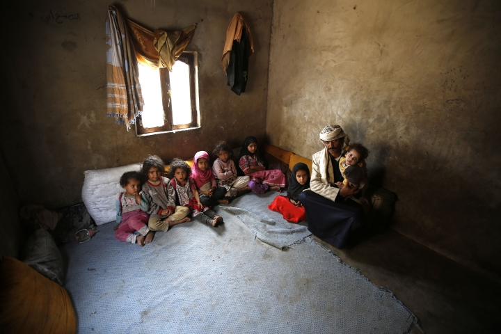 FILE - In this March 28, 2016 file photo, Faisal Ahmed, whose infant son, Udai Faisal, died of severe acute malnutrition, sits with his nine remaining children at his house in Hazyaz village on the southern outskirts of Sanaa, Yemen. Save the Children, an international aid group said late Wednesday, Nov. 15, 2017, that an estimated 130 children or more die every day in war-torn Yemen from extreme hunger and disease. It said a continuing blockade by the Saudi-led coalition fighting Yemen's Shiite rebels is likely to further increase the death rate and that over 50,000 children are believed to have died in 2017. (AP Photo/Hani Mohammed, File)