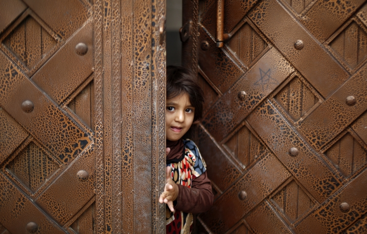 FILE - In this Aug. 15, 2015 file photo, a Yemeni child stands at a door as she waits to receive a polio vaccination during a house-to-house polio immunization campaign in Sanaa, Yemen. Save the Children, an international aid group said late Wednesday, Nov. 15, 2017, that an estimated 130 children or more die every day in war-torn Yemen from extreme hunger and disease. It said a continuing blockade by the Saudi-led coalition fighting Yemen's Shiite rebels is likely to further increase the death rate and that over 50,000 children are believed to have died in 2017. (AP Photo/Hani Mohammed, File)