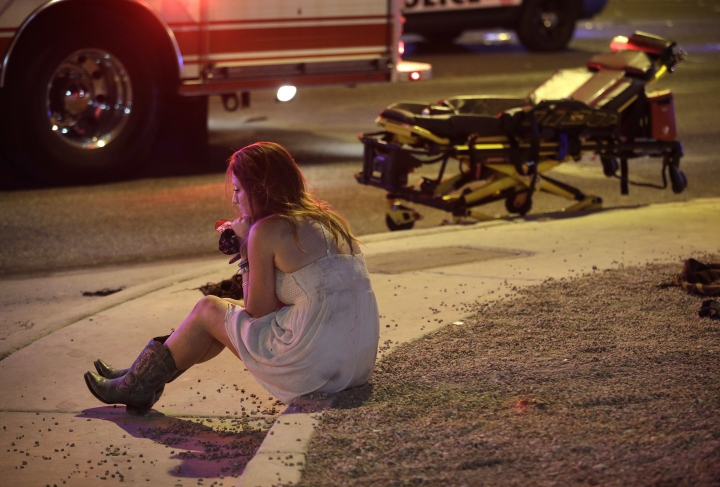 FILE - In this Oct. 2, 2017 file photo, a woman sits on a curb at the scene of a shooting outside of a music festival along the Las Vegas Strip, in Las Vegas. It came as little surprise to producers, but Showtime's documentary series this fall on mass shooting incidents was itself disrupted by mass shootings. The network cut back on reruns of the series following the Oct. 1 attack at a country music concert in Las Vegas that killed 58 people and injured hundreds. An episode that identified the 2016 Orlando nightclub shooting as the nation's most deadly event had to be changed because Las Vegas made that fact outdated.(AP Photo/John Locher, File)
