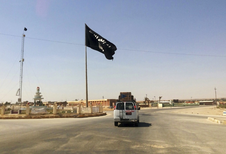 FILE - This Tuesday, July 22, 2014 file photo shows a motorist passing by a flag of the Islamic State group in central Rawah, 175 miles (281 kilometers) northwest of Baghdad, Iraq. Iraq's Defense Ministry said Friday, Nov. 17, 2017 Iraqi forces have retaken the last IS-held town in the country, more than three years after the militant group stormed nearly a third of Iraqi territory.(AP Photo, File)