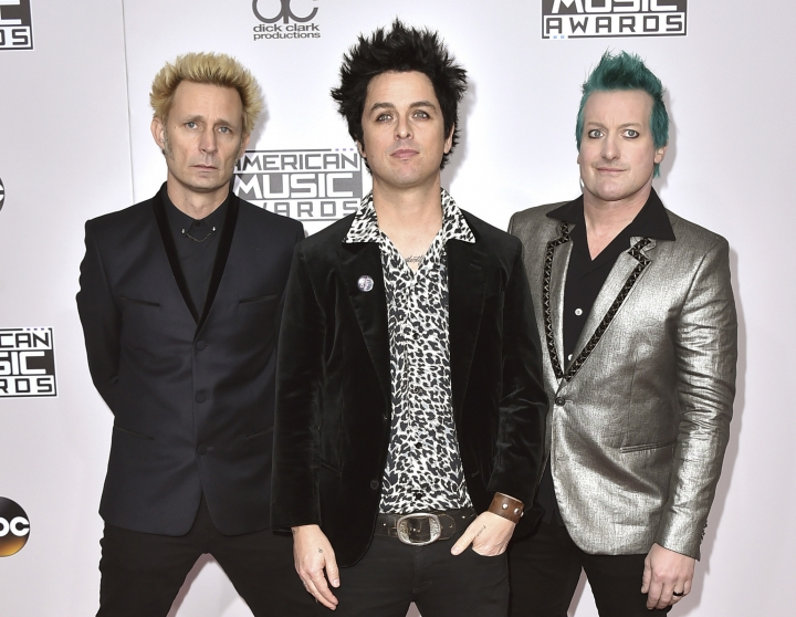 "FILE - In this Nov. 20, 2016 file photo, Mike Dirnt, from left, Billie Joe Armstrong, and Tre Cool, of Green Day, arrive at the American Music Awards in Los Angeles. The band will release their latest, ""Greatest Hits: God's Favorite Band,"" on Friday. (Photo by Jordan Strauss/Invision/AP)"
