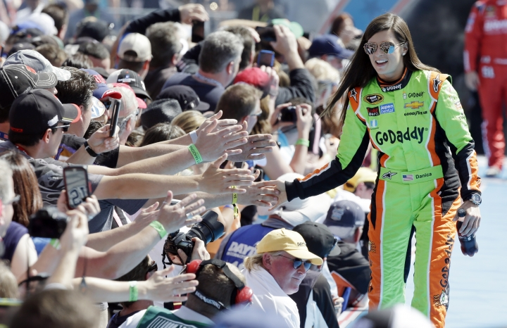 FILE - In this Feb. 22, 2015, file photo, driver Danica Patrick greets fans as she is introduced before the start of the Daytona 500 NASCAR Sprint Cup series auto race at Daytona International Speedway in Daytona Beach, Fla. Patrick announced plans Friday, Nov. 17, 2017, to run just 2 races in 2018, the Daytona 500 and the Indianapolis 500, and end her full-time driving career. (AP Photo/John Raoux, File)