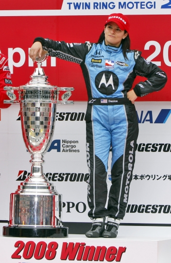 FILE - In this April 20, 2008, file photo, American Danica Patrick, of Andretti Green Racing, poses alongside the trophy on the podium after winning the IndyCar auto race at Twin Ring Motegi in Motegi, Japan. Patrick announced plans Friday, Nov. 17, 2017, to run just 2 races in 2018, the Daytona 500 and the Indianapolis 500, and end her full-time driving career. (AP Photo/Shuji Kajiyama, File)