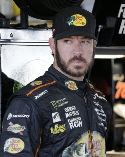 Martin Truex Jr. stands in the garage before practice for a NASCAR Cup Series auto race at Homestead-Miami Speedway in Homestead, Fla., Saturday, Nov. 18, 2017. (AP Photo/Terry Renna)