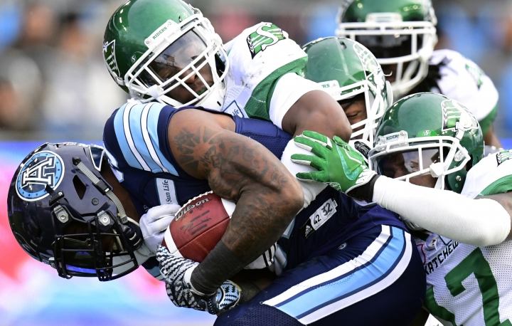 Toronto Argonauts running back James Wilder Jr., left, is wrapped up by Saskatchewan Roughriders defenders during first-half CFL Eastern final football game action, Sunday, Nov. 19, 2017, in Toronto. (Frank Gunn/The Canadian Press via AP)