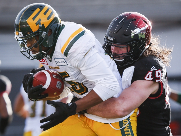 Edmonton Eskimos' Vidal Hazelton, left, is tackled by Calgary Stampeders' Alex Singleton during first quarter CFL West Final football action in Calgary, Sunday, Nov. 19, 2017. (Todd Korol/The Canadian Press via AP)
