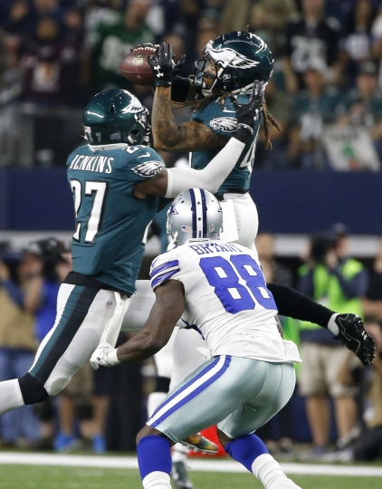Philadelphia Eagles safety Malcolm Jenkins (27) and Dallas Cowboys wide receiver Dez Bryant (88) watch as the Eagles' Ronald Darby, top, intercepts a pass intended for Bryant in the first half of an NFL football game, Sunday, Nov. 19, 2017, in Arlington, Texas. (AP Photo/Ron Jenkins)