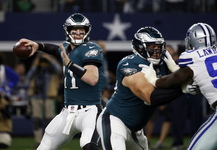 Philadelphia Eagles quarterback Carson Wentz throws a pass under pressure from Dallas Cowboys' DeMarcus Lawrence (90) in the first half of an NFL football game, Sunday, Nov. 19, 2017, in Arlington, Texas. (AP Photo/Ron Jenkins)