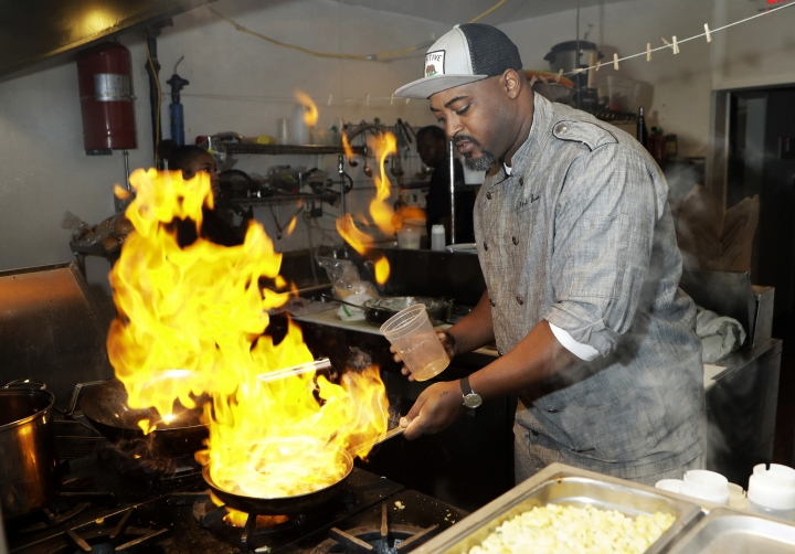 """In a photo from Friday, Nov. 17, 2017, in Detroit, River Bistro chef Maxcel Hardy prepares a Caribbean shrimp dish at his restaurant. The city allows chefs and prospective restaurant owners to realize their dreams at a lower financial cost than other places, like New York, according to chef Hardy. """"If you had a passion and a dream to open a restaurant, Detroit is one of those areas where you can do it and at a decent price,"""" said Hardy. (AP Photo/Carlos Osorio)"""