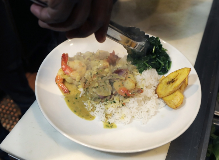 "In a photo from Friday, Nov. 17, 2017, in Detroit, River Bistro chef Maxcel Hardy plates a Caribbean shrimp dish at his restaurant. The city allows chefs and prospective restaurant owners to realize their dreams at a lower financial cost than other places, like New York, according to chef Hardy. ""If you had a passion and a dream to open a restaurant, Detroit is one of those areas where you can do it and at a decent price,"" said Hardy. (AP Photo/Carlos Osorio)"