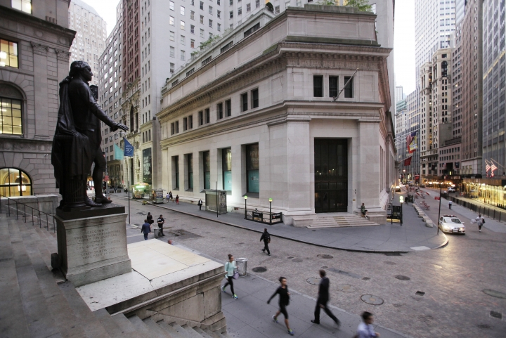 FILE - In this Oct. 8, 2014, file photo, people walk to work on Wall Street beneath a statue of George Washington, in New York. U.S. stocks are opening higher Tuesday, Nov. 21, 2017, as most industries, including technology and health care companies, start the day with solid gains. (AP Photo/Mark Lennihan, File)