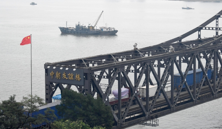 """FILE - In this Sept. 5, 2017, file photo, trucks transport goods to North Korea through the Friendship Bridge linking China and North Korea, as seen from Dandong in northeastern China's Liaoning Province. China has criticized unilateral sanctions and """"long-arm jurisdiction"""" by other governments after Washington penalized Chinese companies accused of trading with North Korea. The Chinese foreign ministry gave no indication whether Beijing might take action in response. (Minoru Iwasaki/Kyodo News via AP)"""