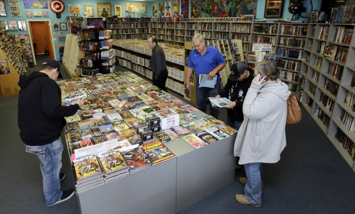 In this Wednesday, Nov. 8, 2017, photo, customers browse for comic books during New Comic Day at Carol & John's Comic Book Shop in Cleveland. John Dudas, who co-owns the shop, recently participated in Local Comic Shop Day, which he calls the comic book industry's equivalent of Black Friday. People lined up outside the store for limited-edition comics, and had a great time while they waited. (AP Photo/Tony Dejak)