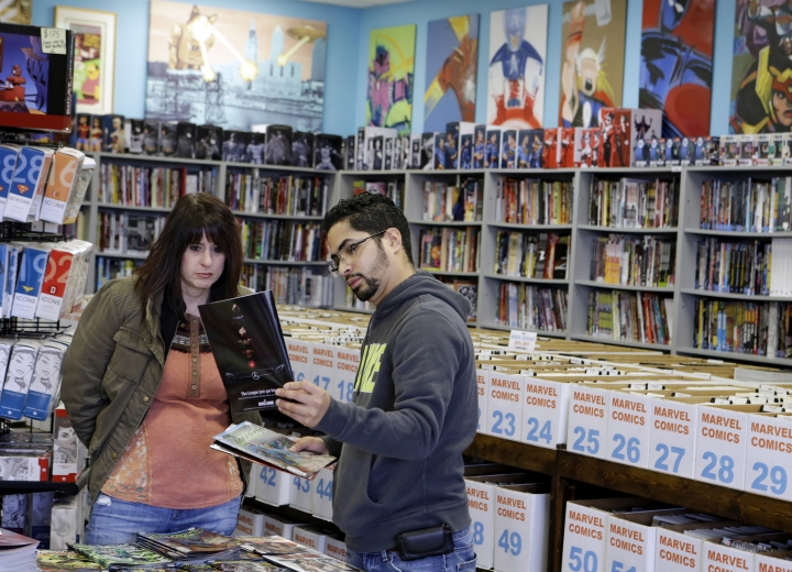 In this Wednesday, Nov. 8, 2017, photo, Christy Abulaban and Abner Rondon look over new releases of comic books during New Comic Day at Carol & John's Comic Book Shop, in Cleveland. John Dudas, who co-owns the shop, recently participated in Local Comic Shop Day, which he calls the comic book industry's equivalent of Black Friday. People lined up outside the store for limited-edition comics, and had a great time while they waited. (AP Photo/Tony Dejak)