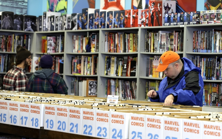 In this Wednesday, Nov. 8, 2017, photo, Robert Cramer, right, 38, searches for comic books during New Comic Day at Carol & John's Comic Book Shop, in Cleveland. Cramer has been collecting since he was 10-years old. John Dudas, who co-owns the shop, recently participated in Local Comic Shop Day, which he calls the comic book industry's equivalent of Black Friday. People lined up outside the store for limited-edition comics, and had a great time while they waited. (AP Photo/Tony Dejak)