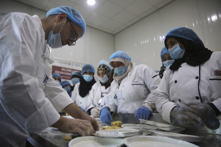 Italian chef Filippo de Maio teaches Syrian refugee women how to make the Italian staple of gnocchi, or dumplings, and jam-filled pies, in the fenced-in Azraq camp in northern Jordan, Thursday, Nov. 23, 2017. The cooking lesson, part of the global Italian Cuisine Week, was meant to break up the routine in Azraq, perhaps the most restrictive of three Jordanian camps for displaced Syrians. (AP Photo/Omar Akour)
