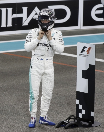 Mercedes driver Valtteri Bottas, of Finland, stands after setting the pole position during the qualifying session at the Yas Marina racetrack in Abu Dhabi, United Arab Emirates, Saturday, Nov. 25, 2017. The Emirates Formula One Grand Prix will take place on Sunday. (AP Photo/Luca Bruno)