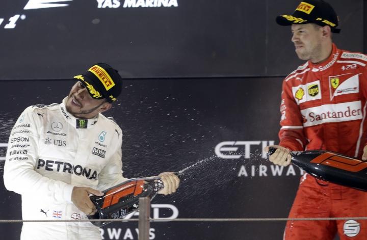 Mercedes driver Lewis Hamilton of Britain, left, and Ferrari driver Sebastian Vettel of Germany celebrate after the Emirates Formula One Grand Prix at the Yas Marina racetrack in Abu Dhabi, United Arab Emirates, Sunday, Nov. 26, 2017. (AP Photo/Luca Bruno)