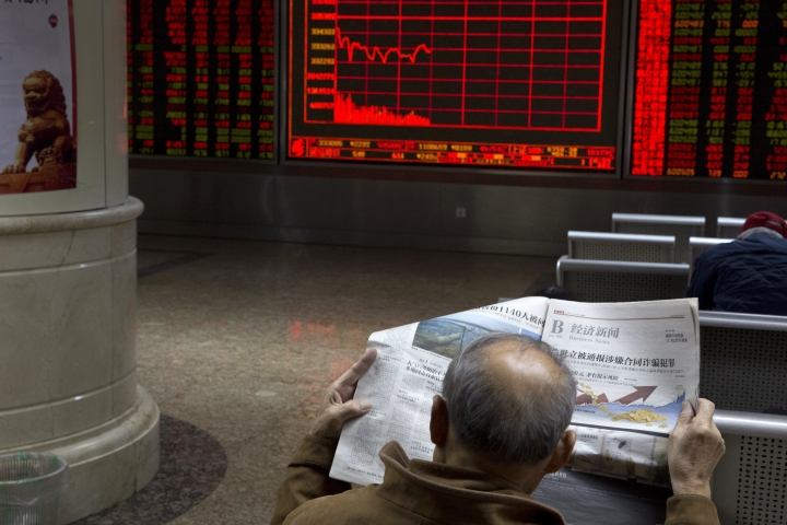 A Chinese man reads a copy of a newspaper near a display for the stock market index in Beijing Monday, Nov. 27, 2017. Asian stock markets tumbled Monday as investors looked ahead to a possible U.S. Senate vote this week on proposed tax changes and a week of economic data announcements. (AP Photo/Ng Han Guan)